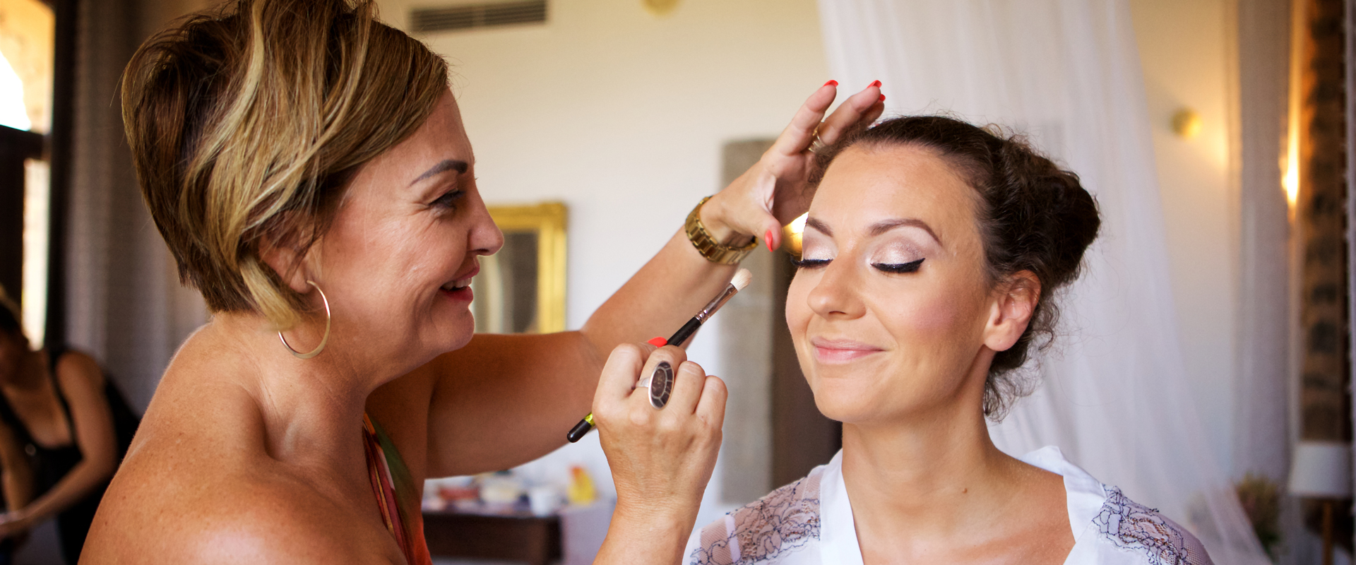 Wedding photograph of bride having her makeup done before her wedding. Photography by ADP London