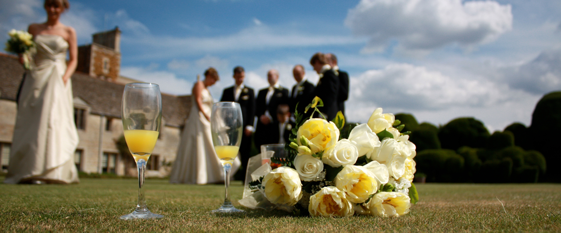 Wedding group photo focused on a bouquet and flute glass. Photography by ADP London